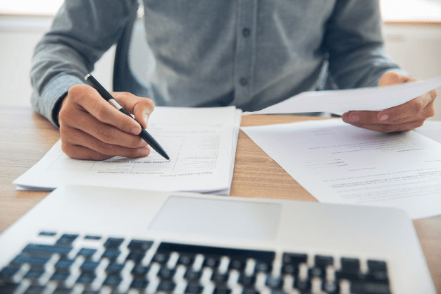 Business man checking organizational documents to ensure compliance