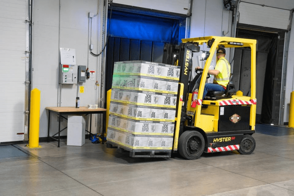 A man on a yellow forklift carrying packages